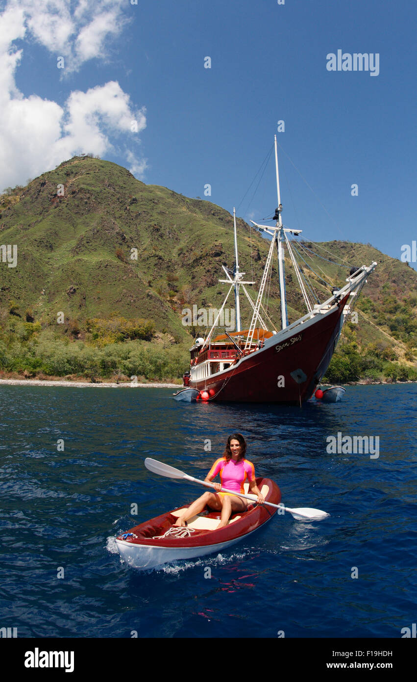 px91346-D. woman (model released) kayaks along Sangeang Island's verdant shores between scuba dives from the - Stock Image