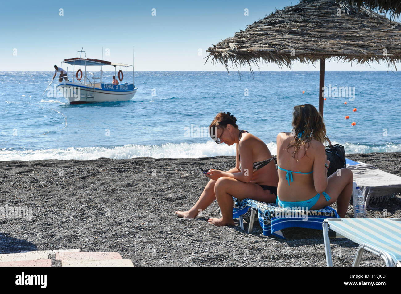 Two female sunbathers under a straw umbrella while a small boat approaching the beach in Kamari, Santorini, Greece. - Stock Image