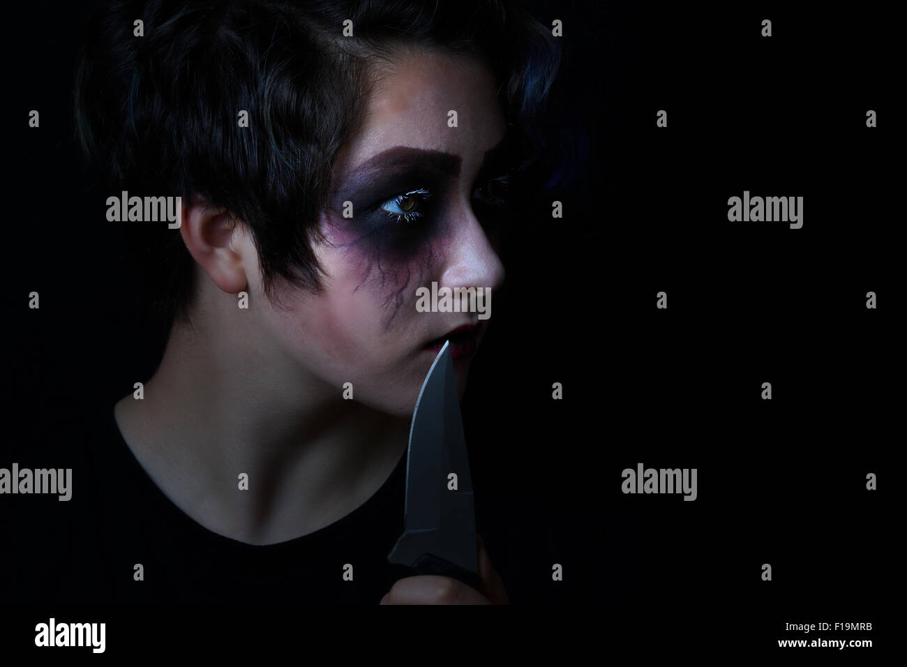 Teen girl masked in scary makeup with combat knife on black background. Stock Photo