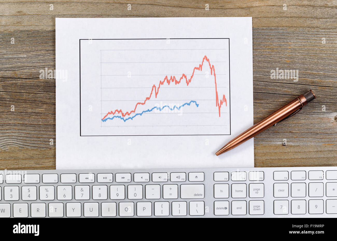 High angled view of line graph, old pen and computer keyboard on rustic desktop. - Stock Image