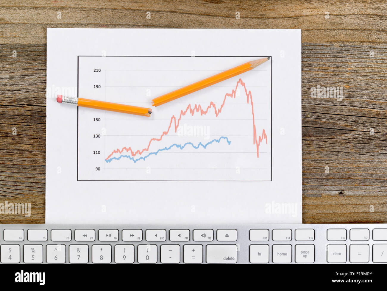 High angled view of line graph, broken pencil and computer keyboard on rustic desktop. - Stock Image