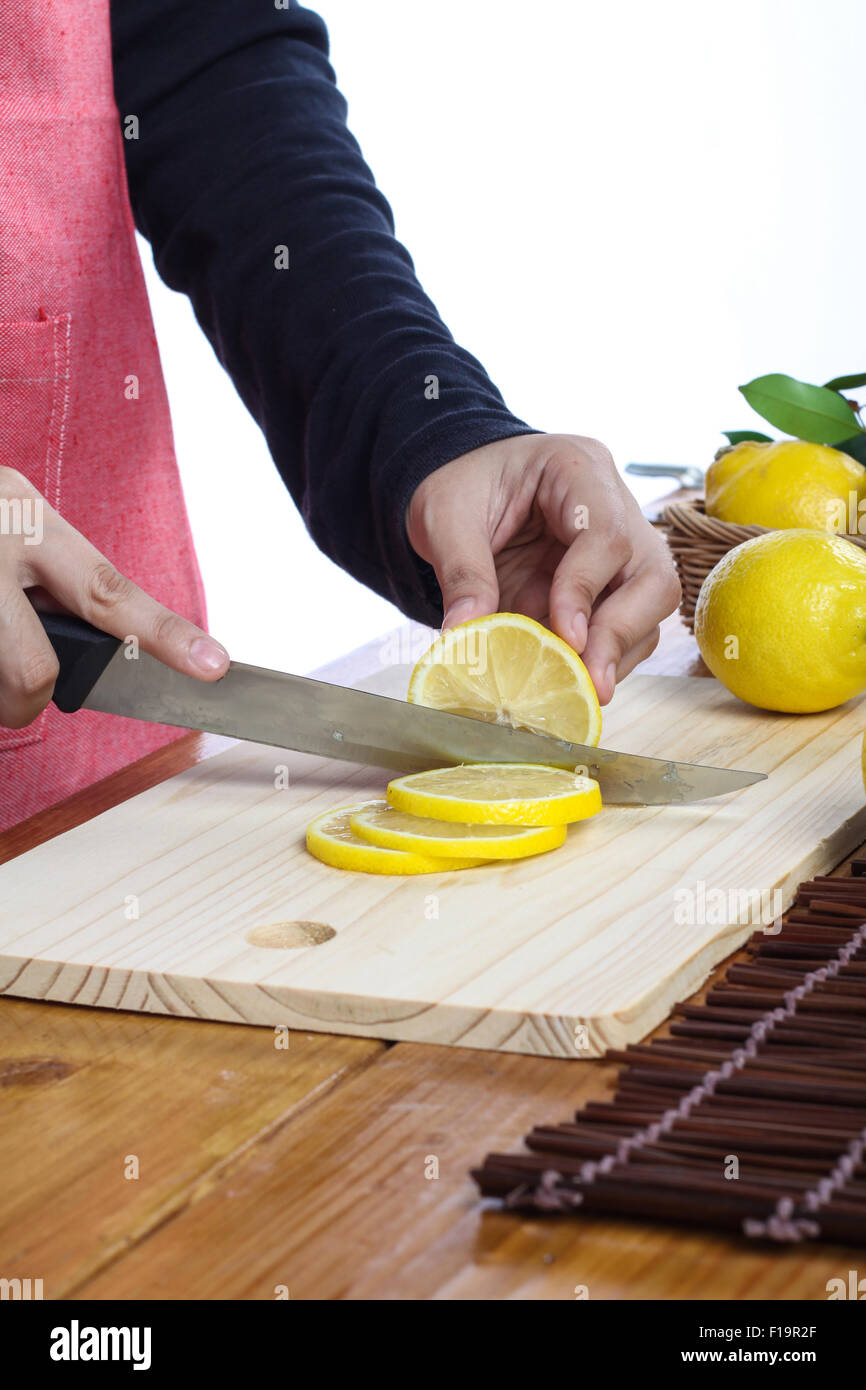 woman cutting lemon in clean environment - Stock Image