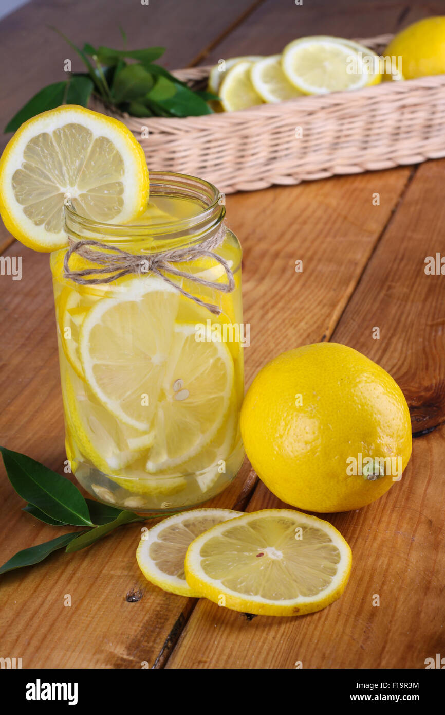 lemonade with some fresh uncut yellow lemon in wooden kitchen table - Stock Image