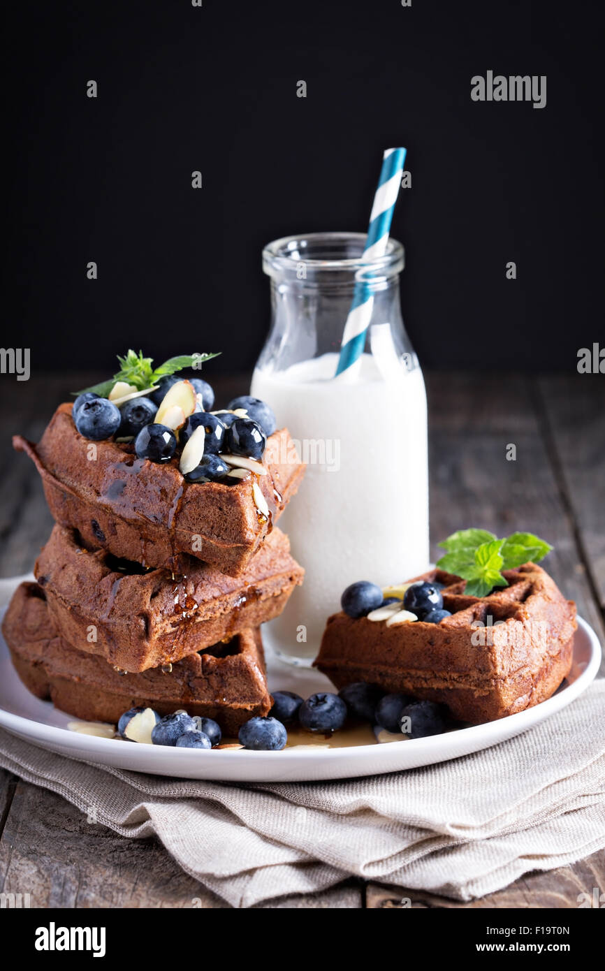 Chocolate waffles with milk and berries for breakfast - Stock Image