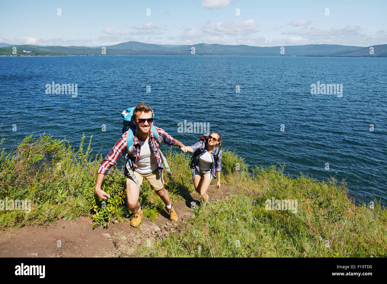 Happy young traveler helping his girlfriend to climb on mount - Stock Image