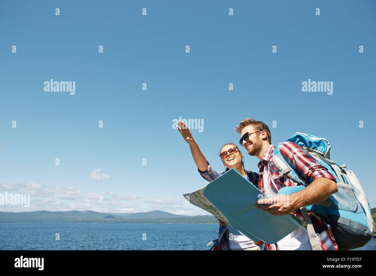 Cheerful hikers with map choosing route for travel - Stock Image