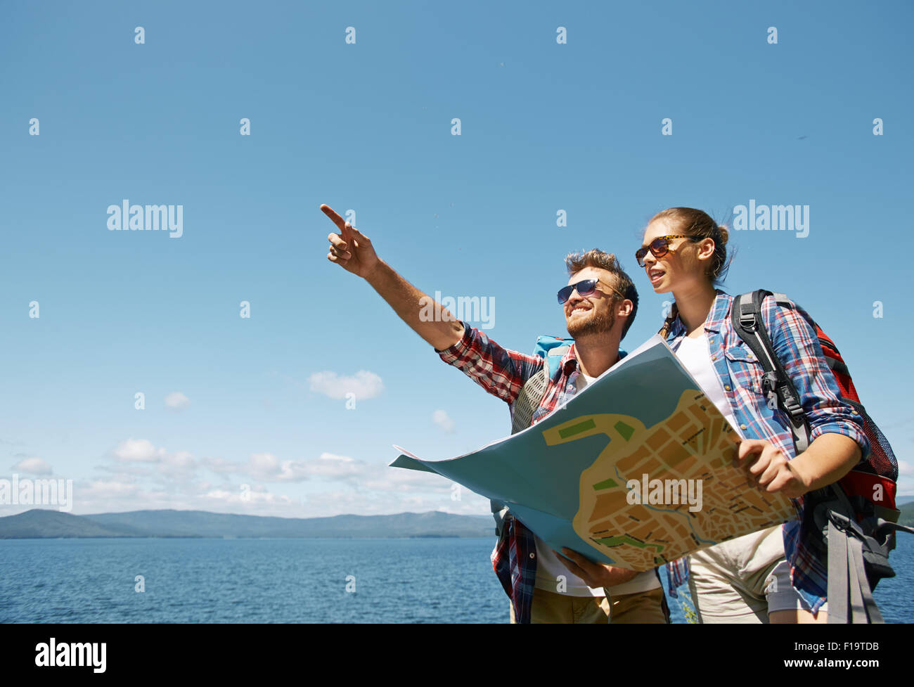 Young couple with map choosing route for further trip - Stock Image