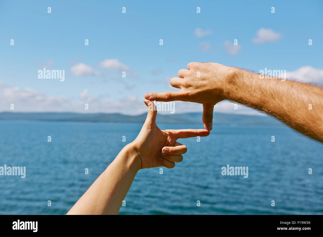Human hands making frame against sea and skyline - Stock Image
