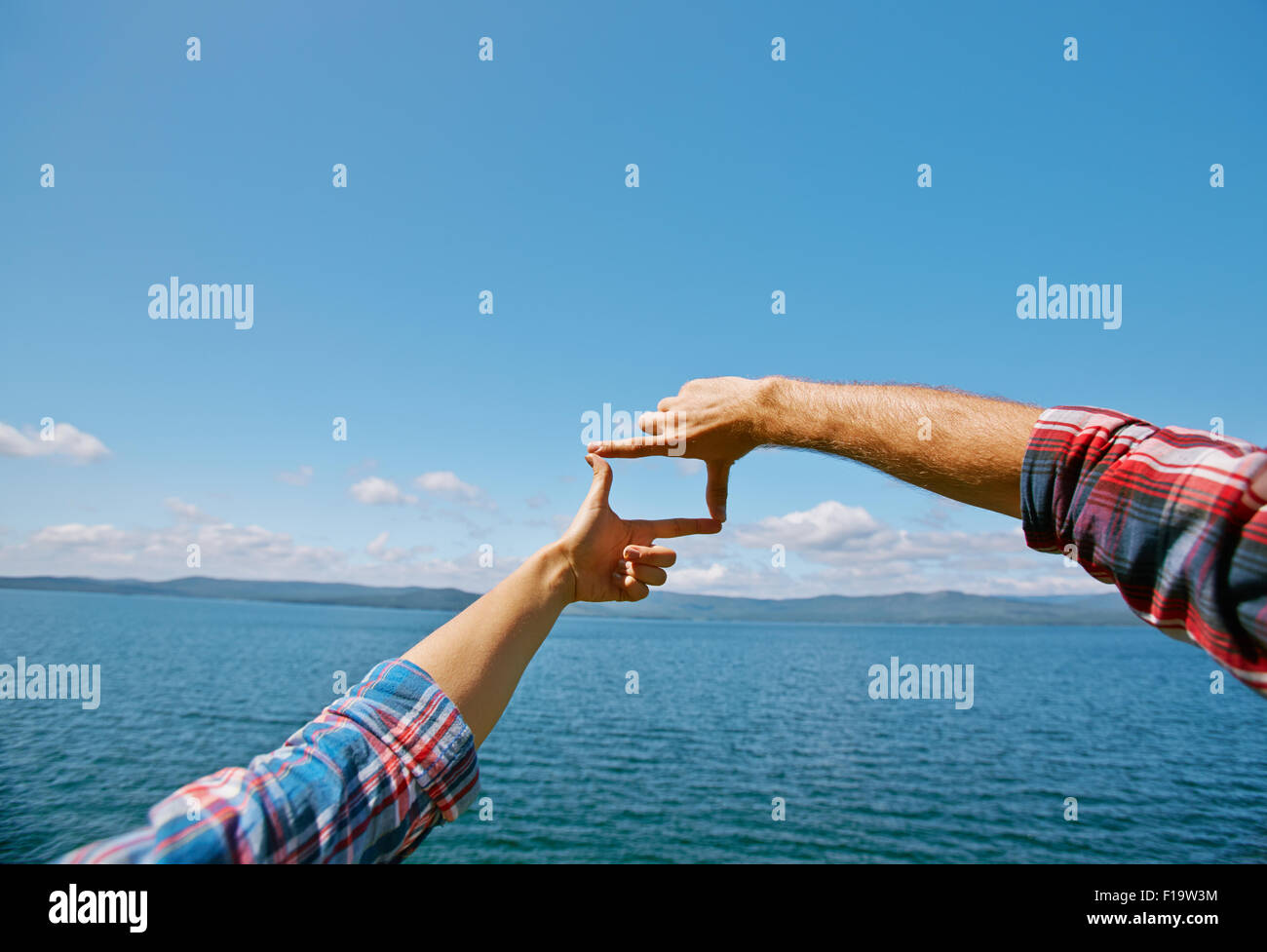 Human hands making frame against blue sky by the seaside - Stock Image