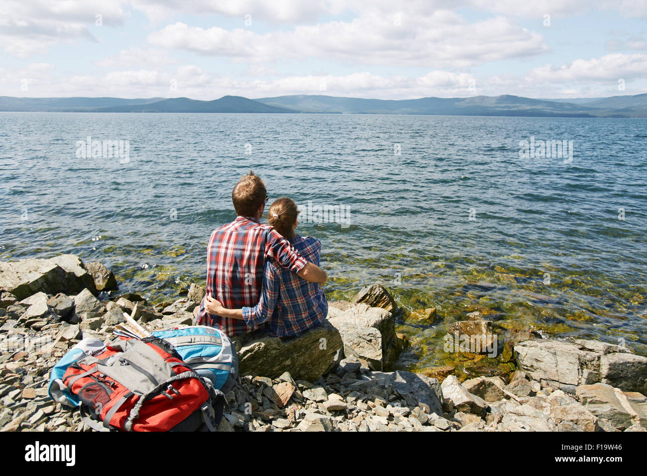 Rear view of amorous romantic couple in embrace sitting by the sea - Stock Image