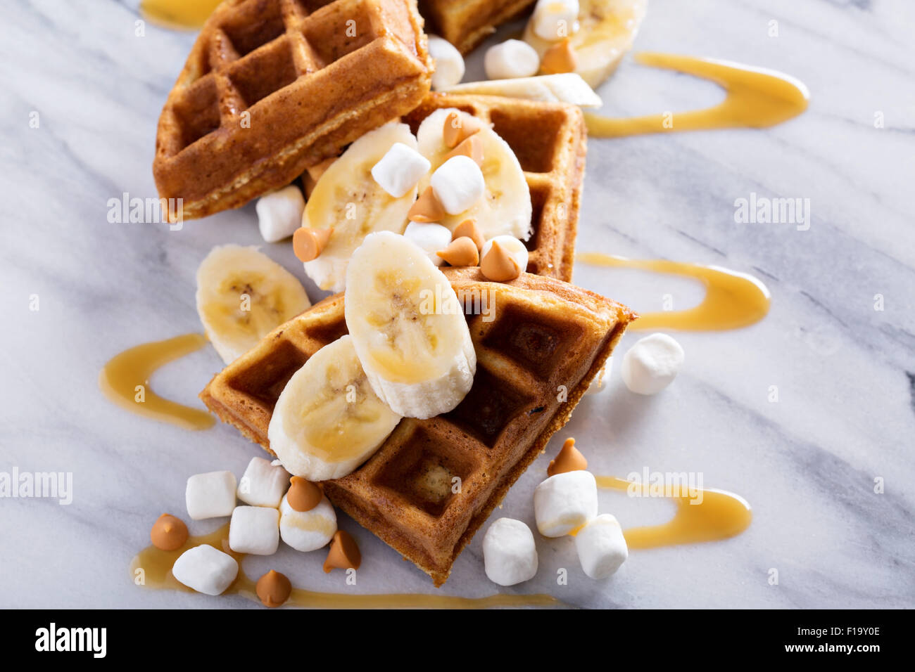 Waffles with peanut butter and bananas topped with caramel syrup - Stock Image