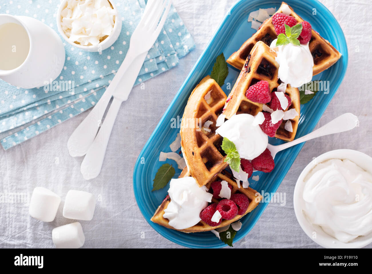 Coconut raspberry waffles served with fresh berries and whipped cream - Stock Image