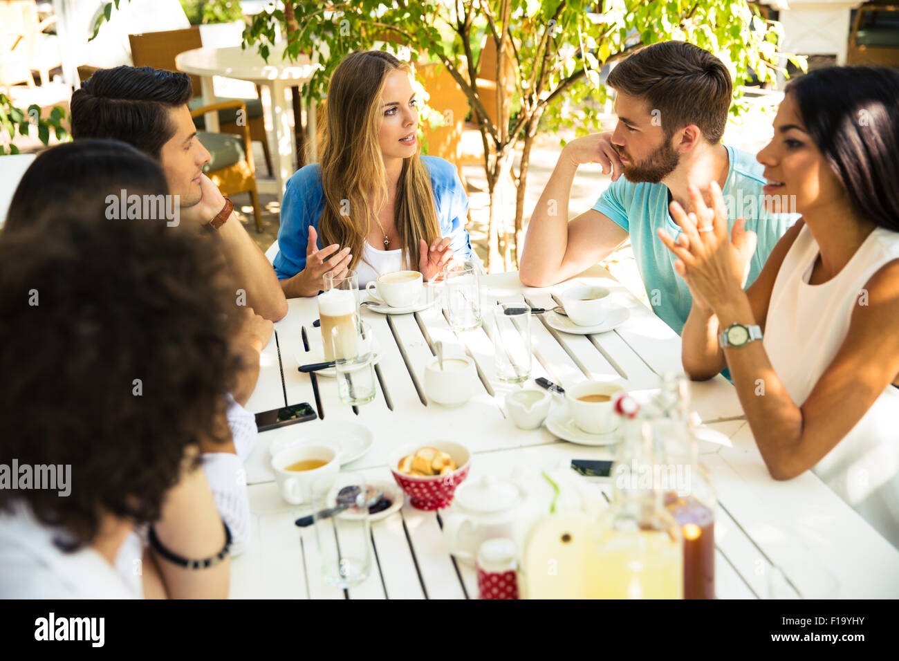 Smiling young friends enjoying meal in outdoor restaurant Stock Photo