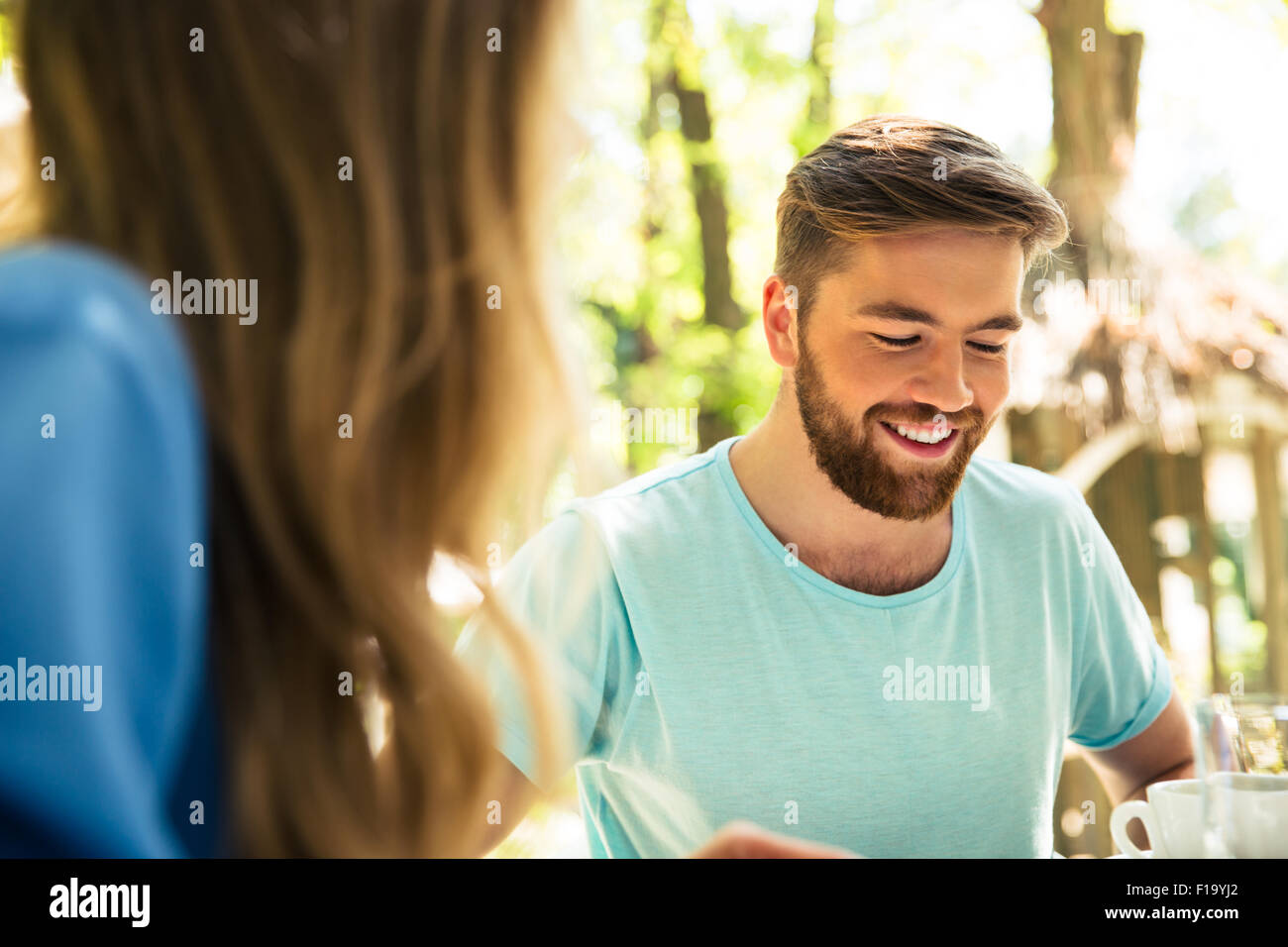 Portrait of a happy friends sitting in outdoors restaurant - Stock Image