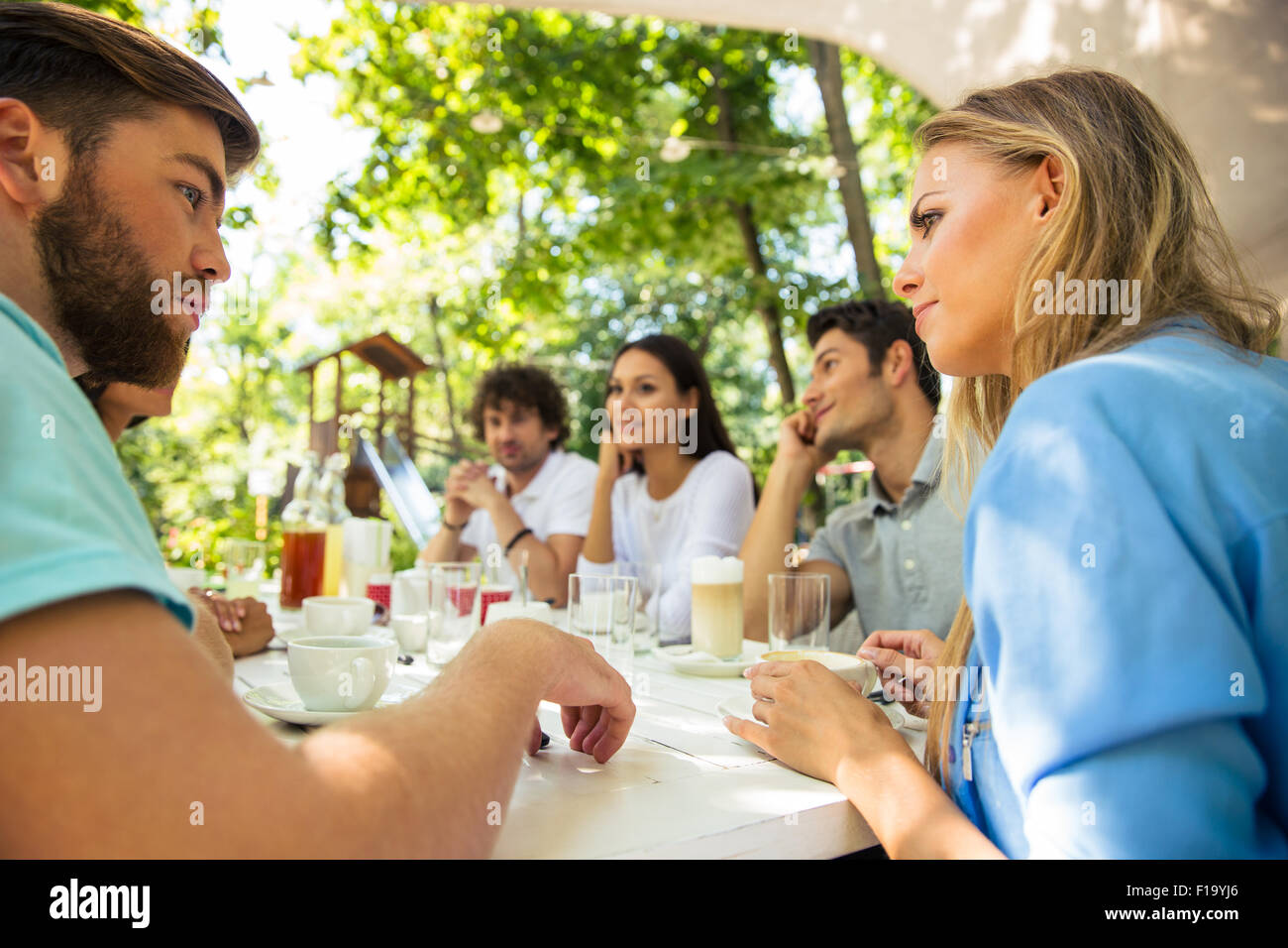 Group of a happy friends sitting at the table in outdoor restaurant Stock Photo