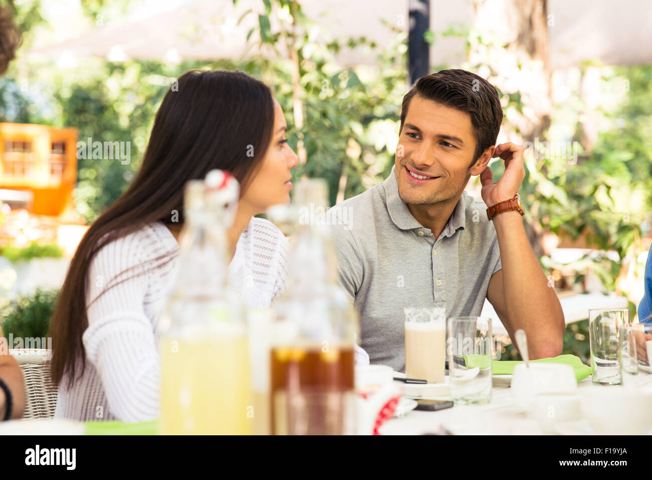 Portrait of a happy couple sitting in outdoor restaurant - Stock Image