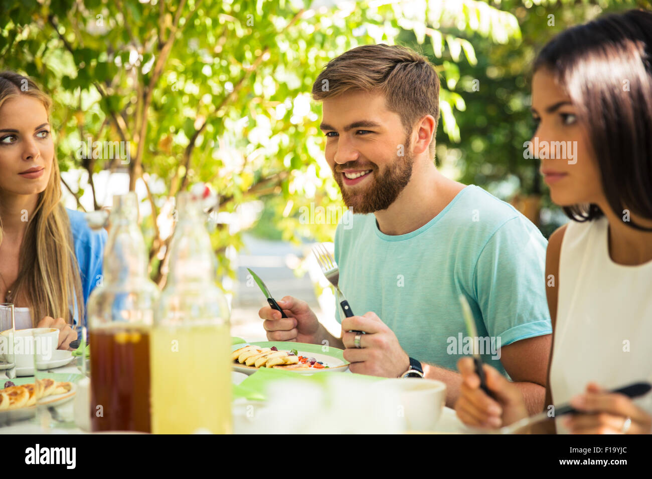 Group of a smiling friends sitting in outdoor restaurant Stock Photo