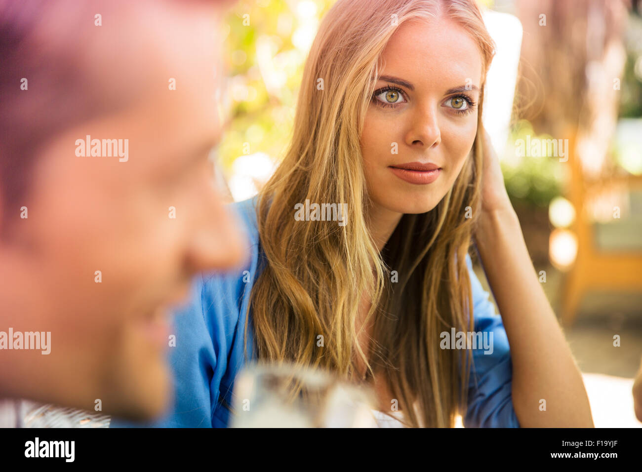 Portrait of a young woman sitting in outdoor restaurant with her friends - Stock Image