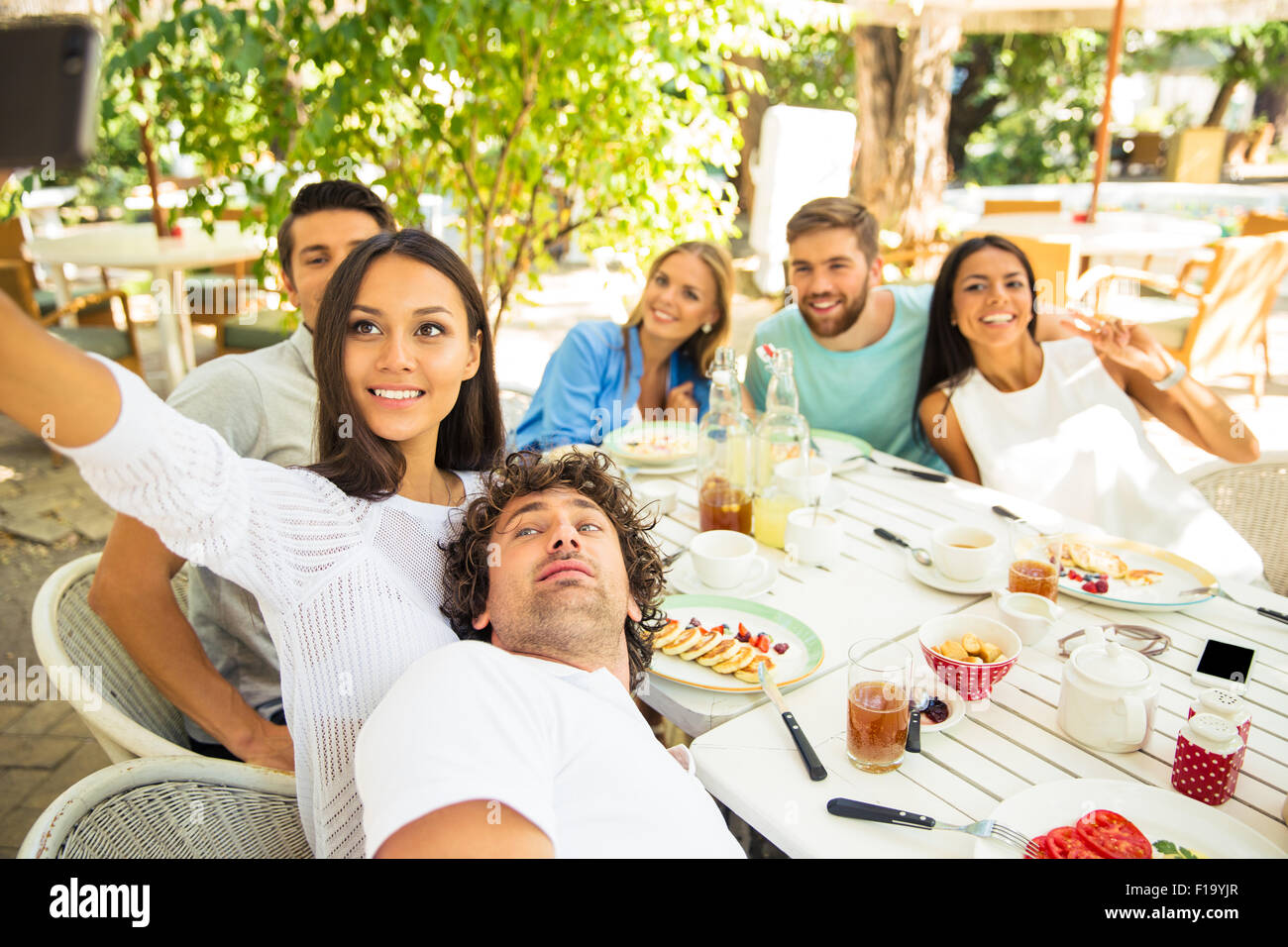 Portrait of a happy friends making selfie photo in outdoor restaurant - Stock Image