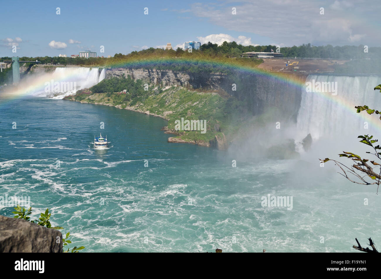 View of American Falls and Horseshoe Falls from Canadian side of Niagara Falls. Rainbow over water.  Maid of the - Stock Image