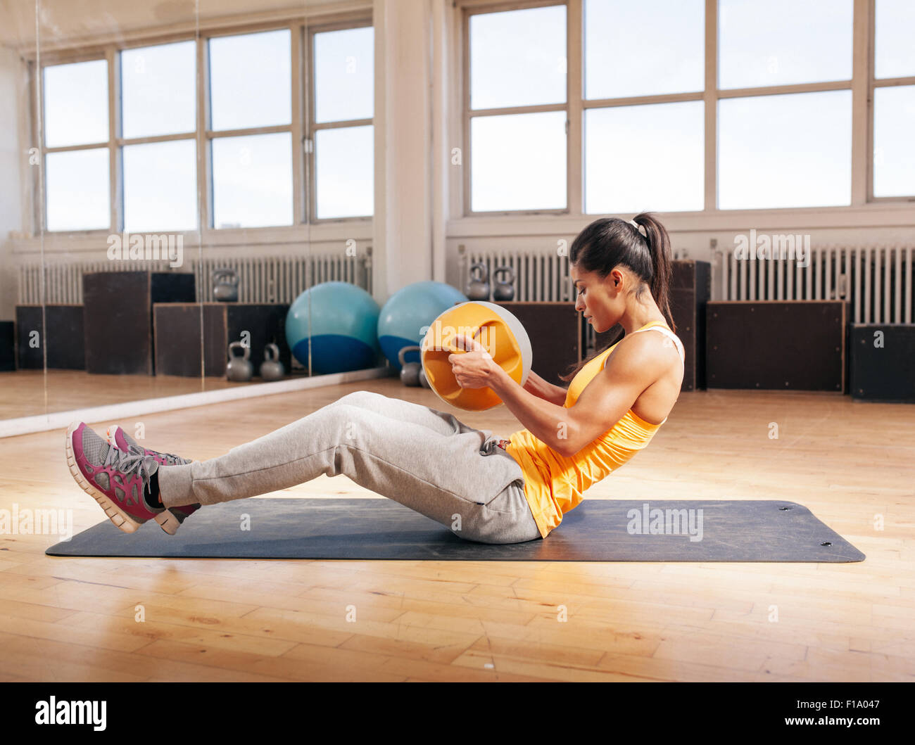 Side view shot of muscular young woman doing crossfit workout using kettlebell. Fitness model exercising in gym. - Stock Image