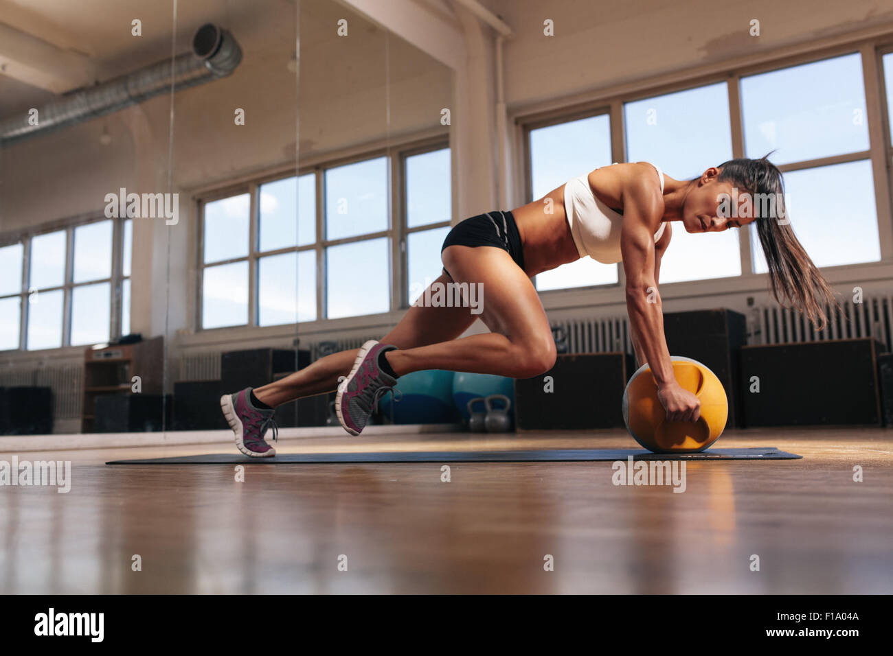 Portrait of a fit and muscular woman doing intense core workout with kettlebell in gym. Female exercising at crossfit - Stock Image