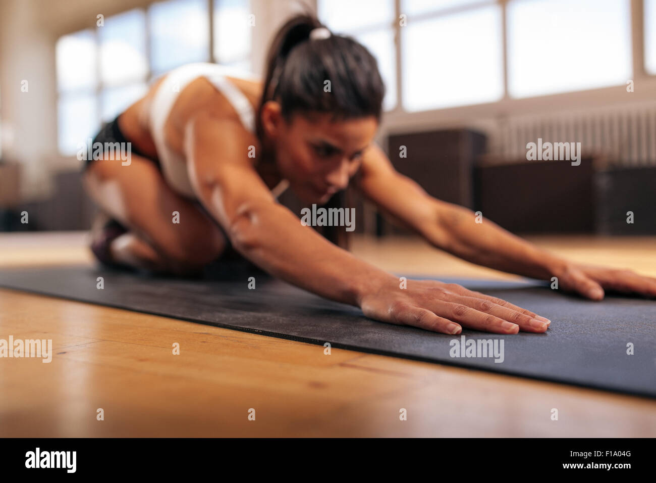 Woman doing stretching workout on fitness mat, focus on hands, fitness female performing yoga on exercise mat at - Stock Image