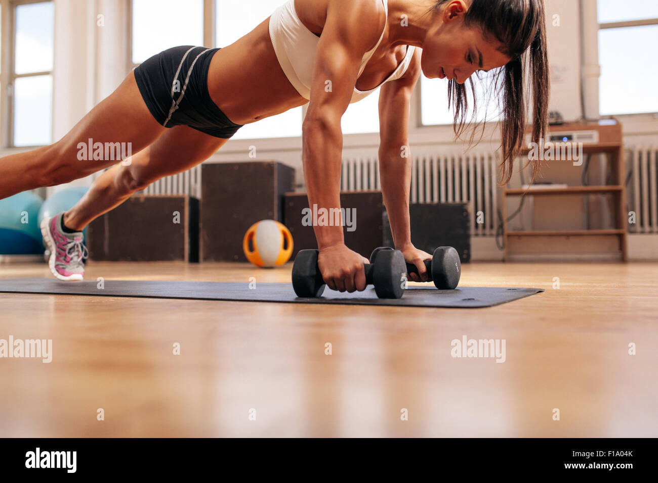 Strong young woman doing push ups exercise with dumbbells on yoga mat. Fitness model doing intense training in the - Stock Image