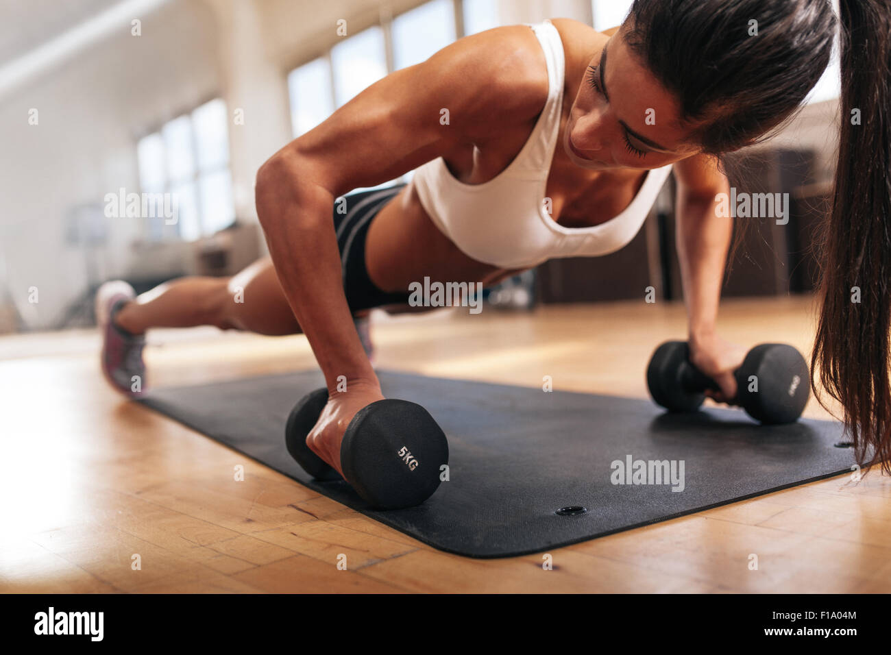 Gym woman doing push-up exercise with dumbbell. Strong female doing crossfit workout. - Stock Image