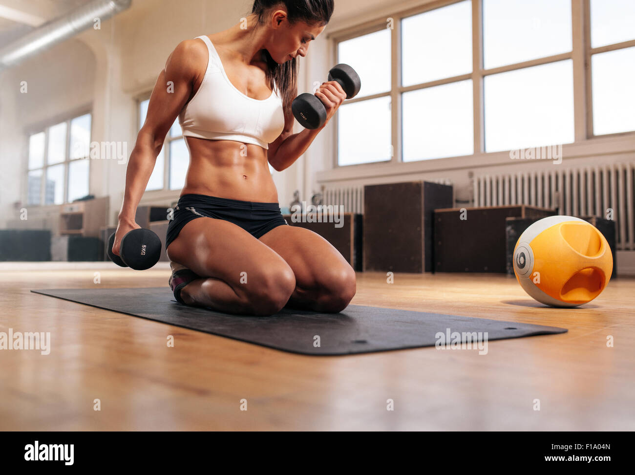 Physically fit woman at the gym lifting dumbbells to strengthen her arms and biceps. Muscular woman sitting on exercise - Stock Image