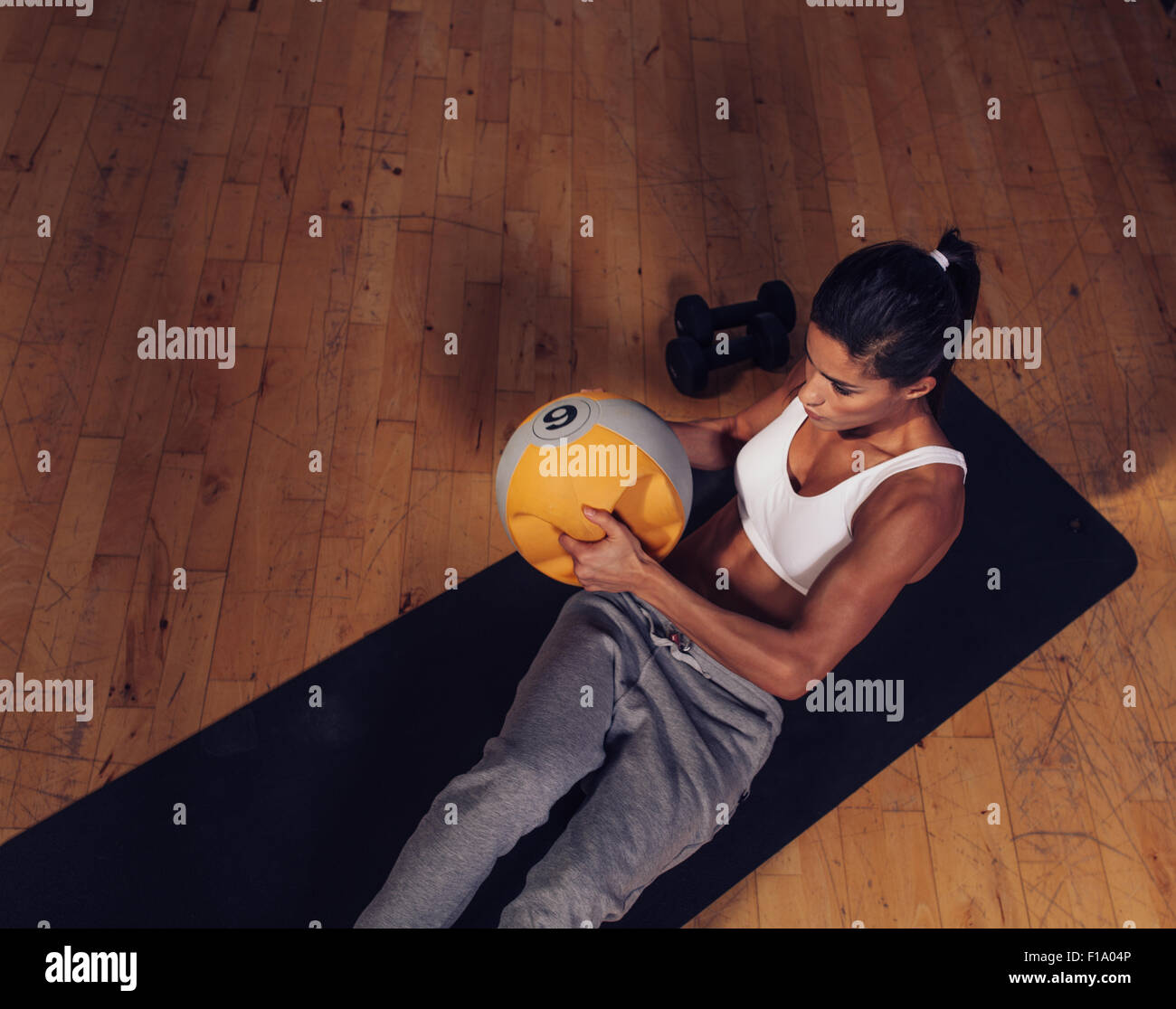 Top view of strong young woman doing core workout using kettlebell weight. Muscular female exercising on fitness - Stock Image