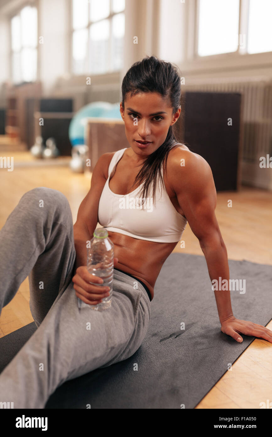 Young woman sitting on fitness mat holding water bottle. Fitness female relaxing after exercise. - Stock Image