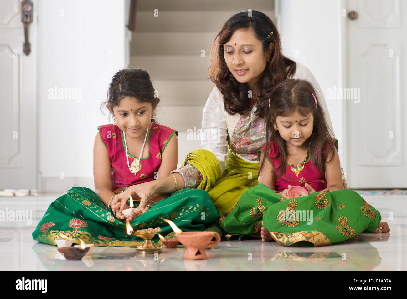 Indian family in traditional sari lighting oil lamp and celebrating Diwali, fesitval of lights at home. - Stock Image