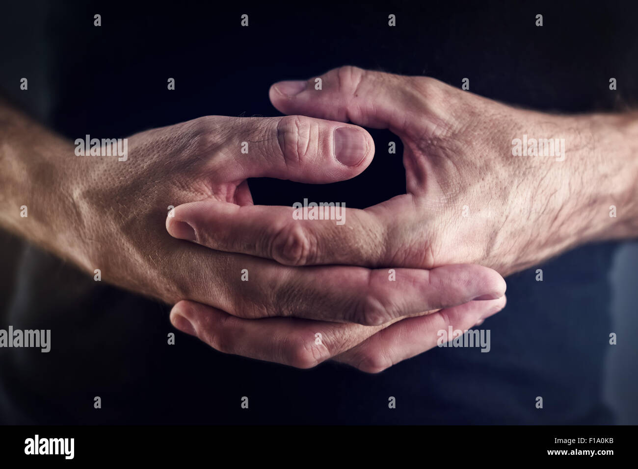 Thumb twiddling, male hands twiddling fingers as an example of time-wasting useless activity, close up selective - Stock Image