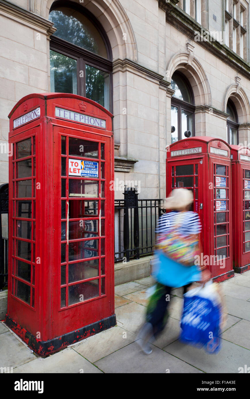 People passing K6 Old type GPO, or BT red Telephone Boxes advertised as being  'To Let' with various uses - Stock Image