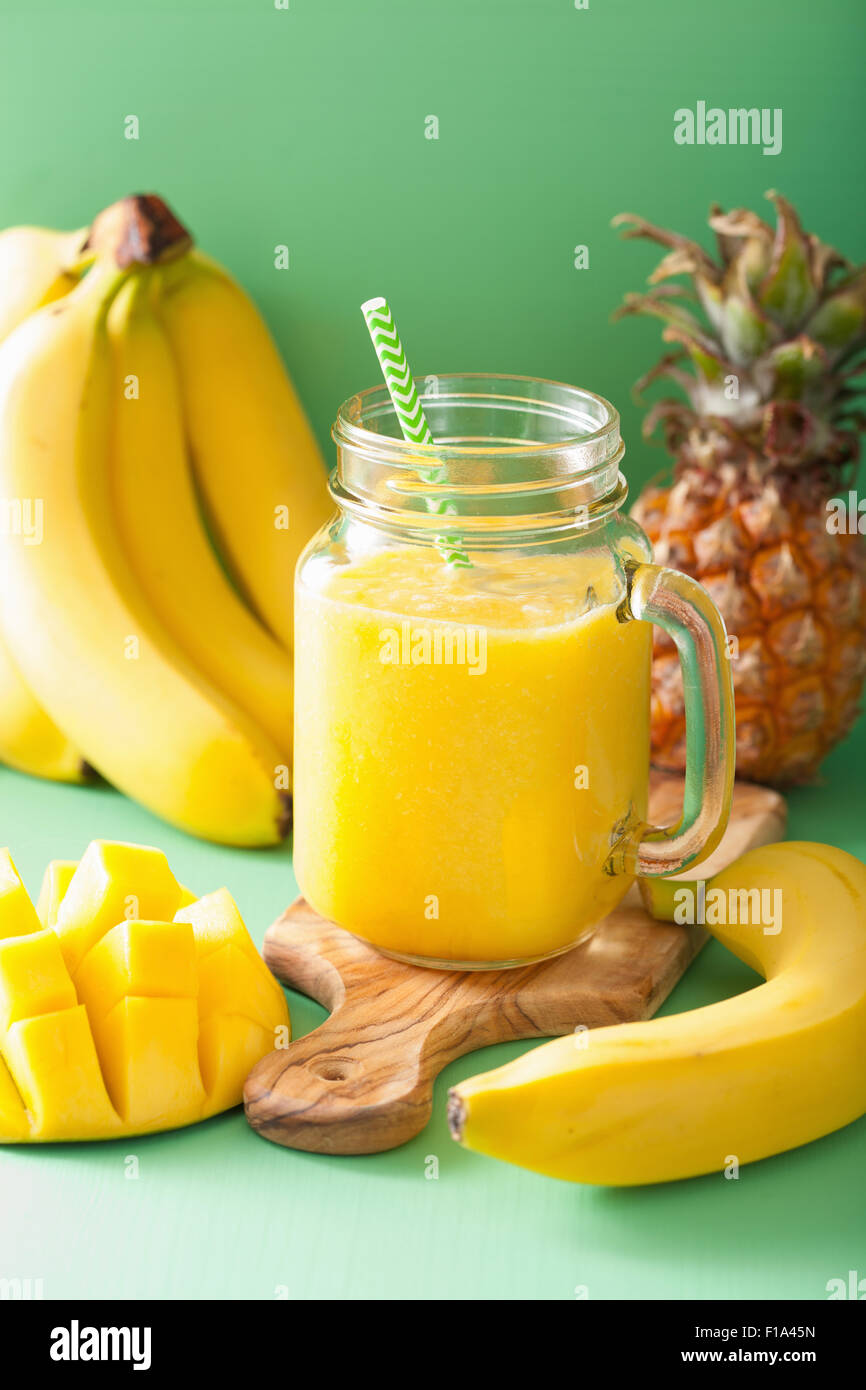 healthy yellow smoothie with mango pineapple banana in mason jars - Stock Image