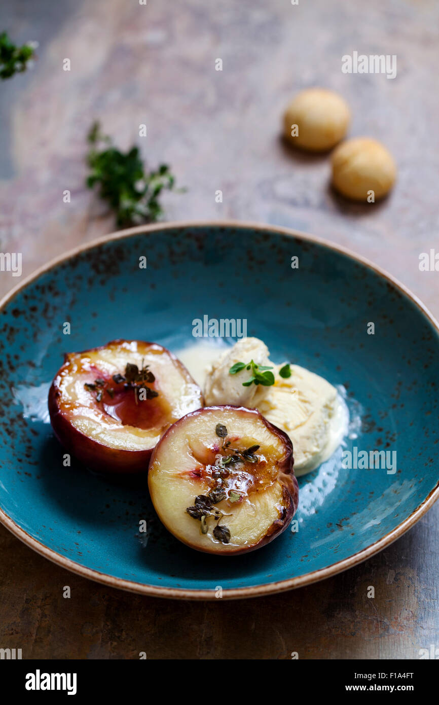Baked peach with thyme, ice cream and amaretti biscuits - Stock Image