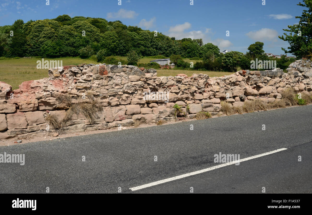 A roadside wall in need of some repair. - Stock Image