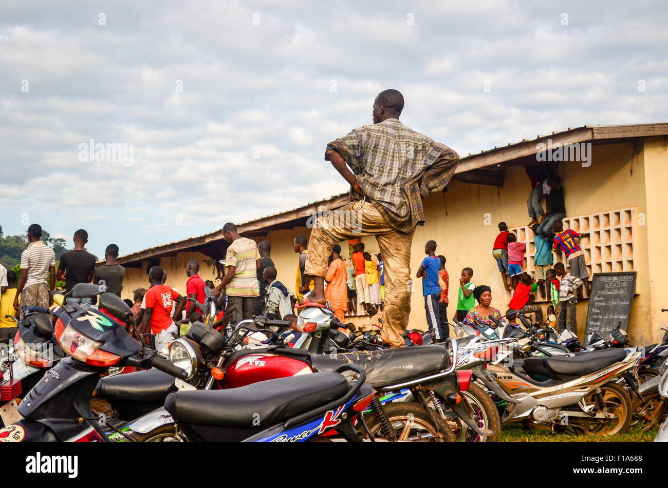 Crowd watching a football game from their motorbikes in Man, Ivory Coast - Stock Image
