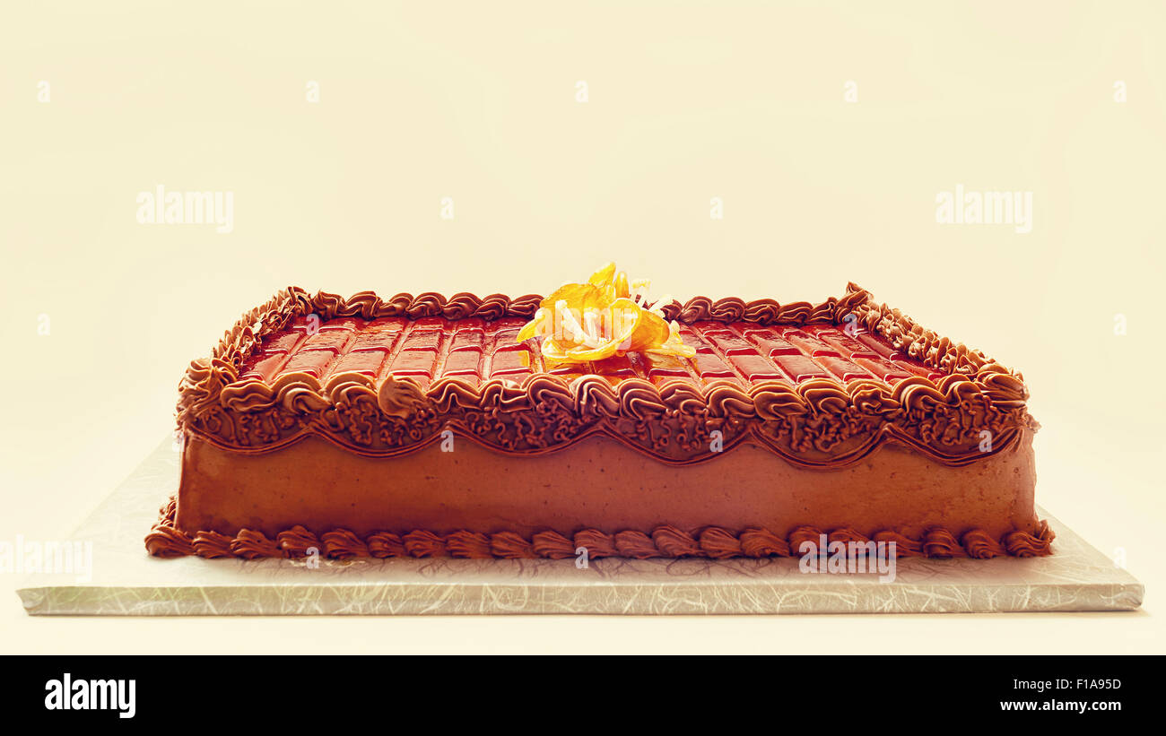 Simple and classical chocolate cake on white background. Details of cream and sugar decoration. - Stock Image