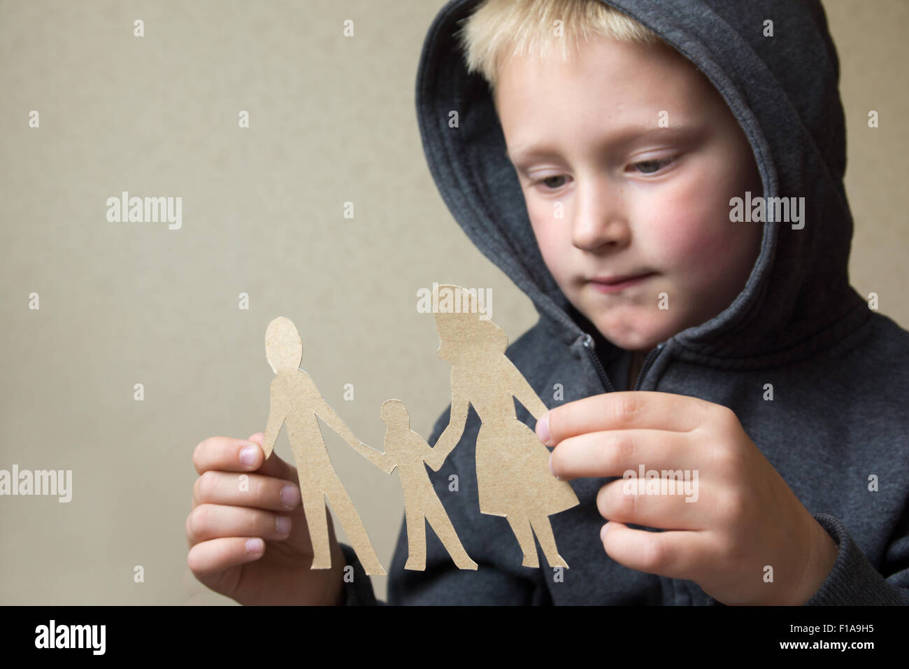 Confused child with paper family, family problems, divorce, suffer concept - Stock Image