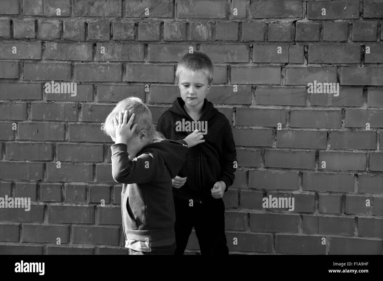 children bullying and fight between two angry aggressive brothers (kids, boys) - Stock Image
