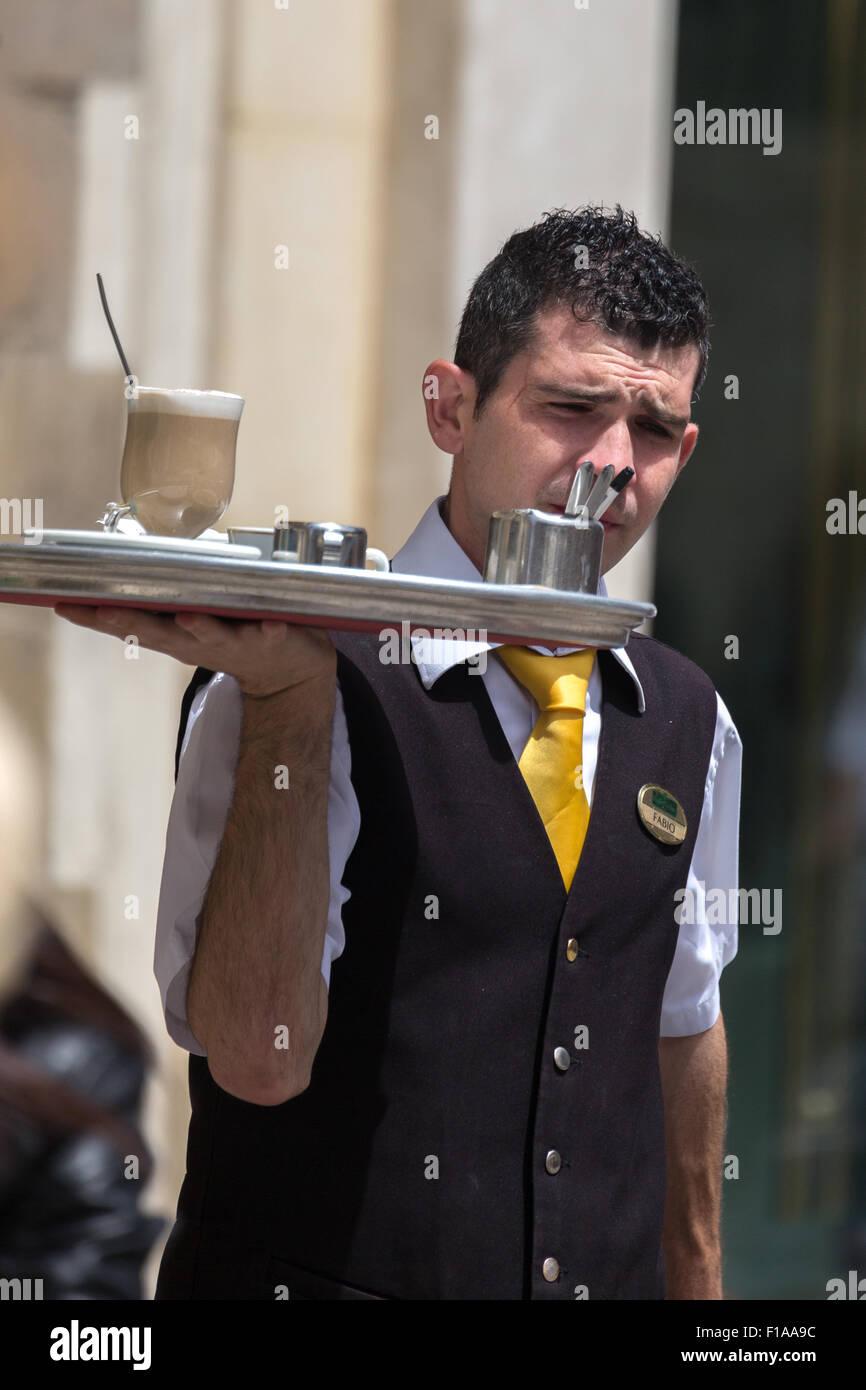 Waiter bringing coffee to outdoor cafe customers. Valletta Malta - Stock Image