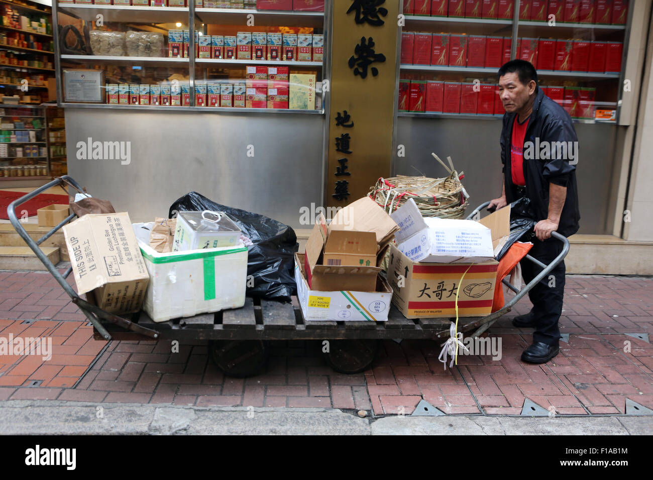 Hong Kong, China, man collects cardboard boxes on a street a Stock Photo