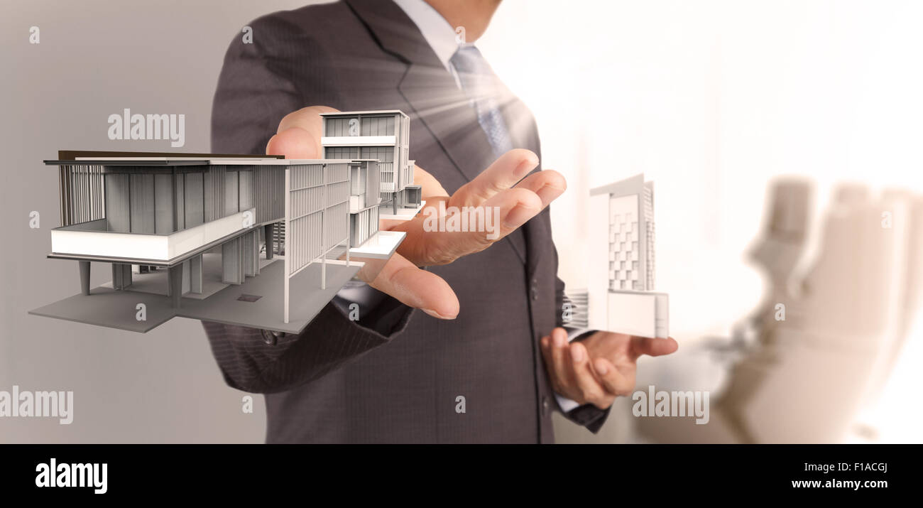 businessman hand presents house model on modern computer as delvelopment concept - Stock Image