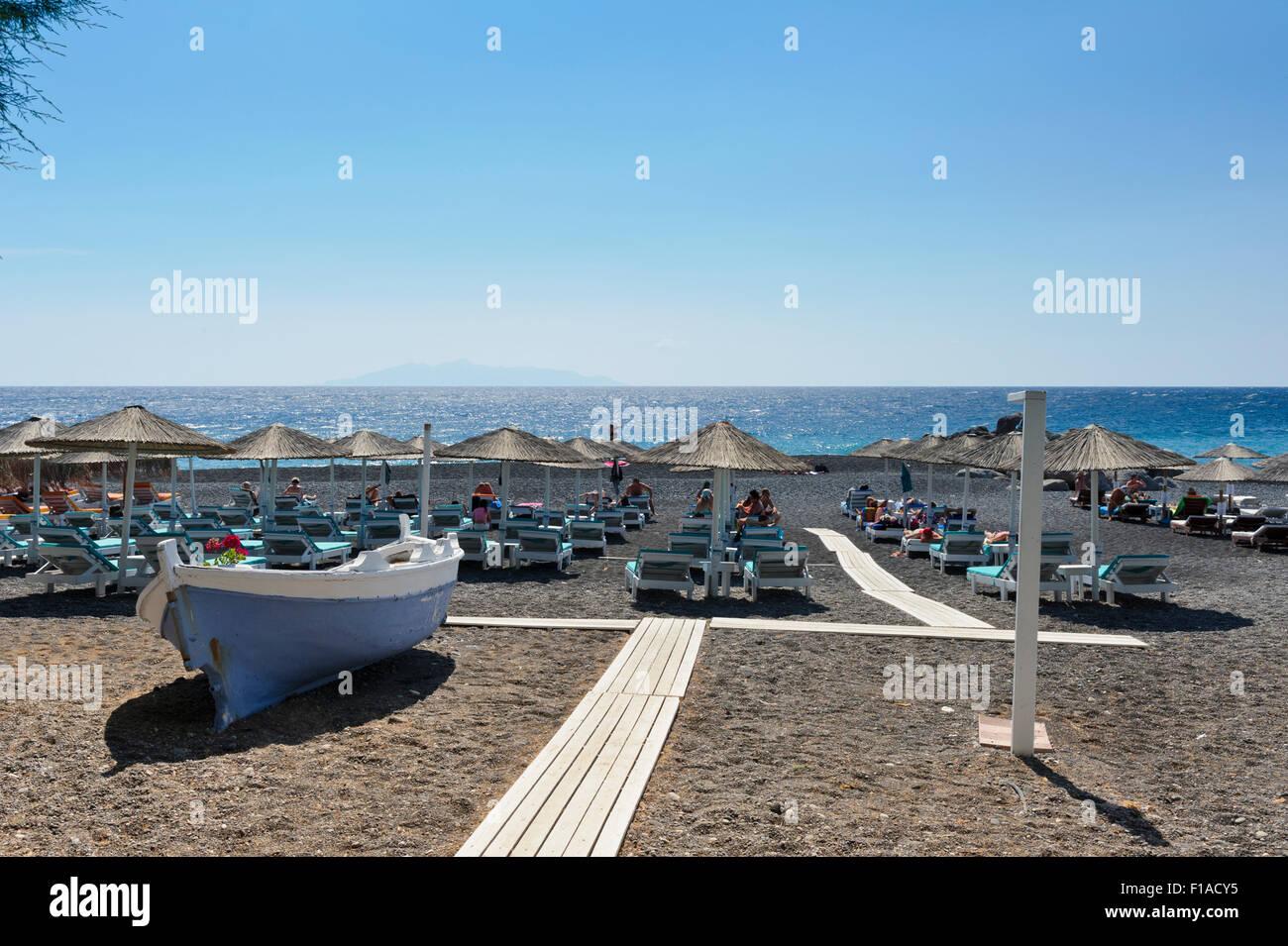 Sunbathers under straw umbrellas on Kamari beach, Santorini, Greece. - Stock Image