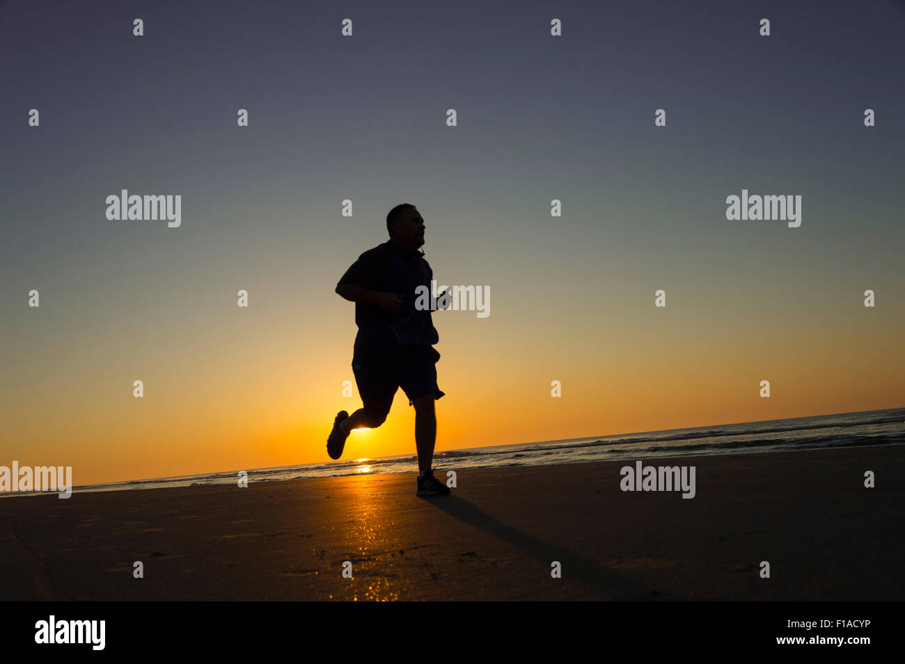 Fat Man Running On Beach At Sunrise - Stock Image