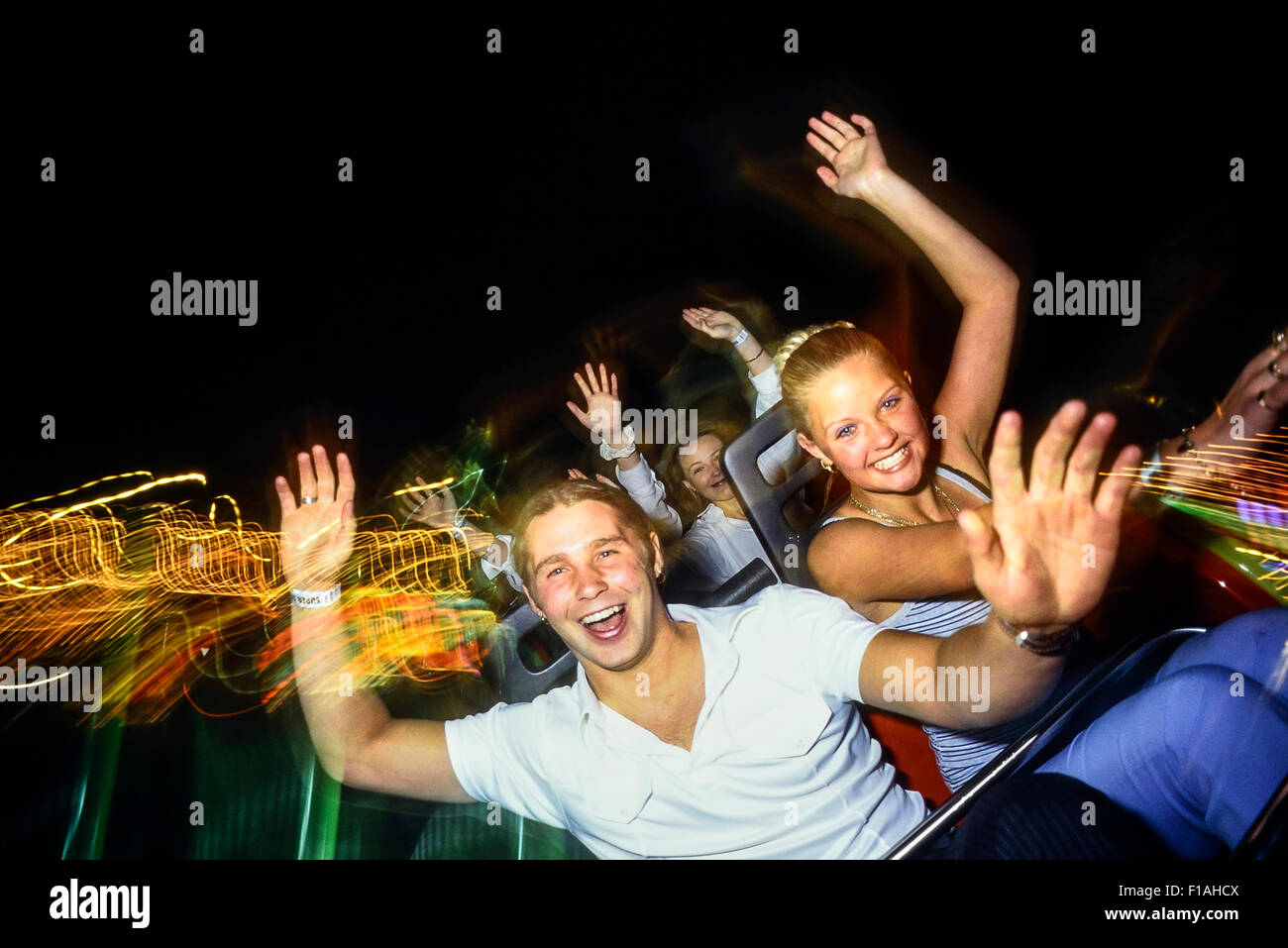A young adult couple enjoying a roller coaster ride at night at Adventure  Island. Southend-on-Sea. Essex. UK