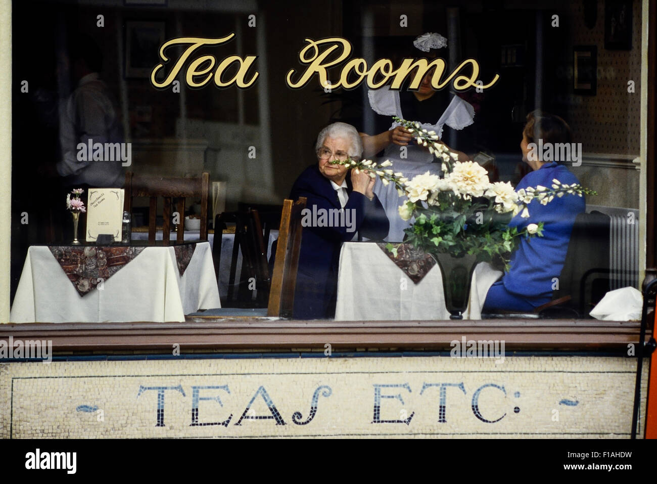 Waitress serving two elderly ladies in a teashop. England. UK - Stock Image