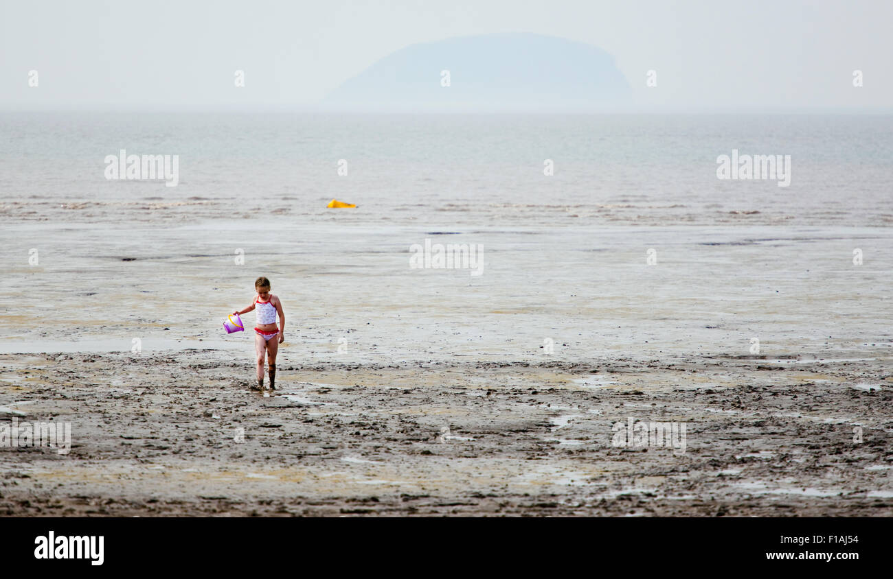 A young girl walking back from a muddy shoreline on an overcast day at a typical english seaside resort. she's covered Stock Photo